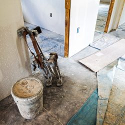 The drywall phase of a home renovation project.  Stilts and a bucket sit in a hallway with tarps partly covering the concrete floor.